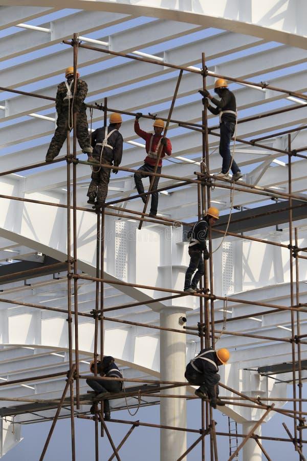 Εργάτες οικοδομών που εργάζονται στα υλικά σκαλωσιάς στοκ φωτογραφίες