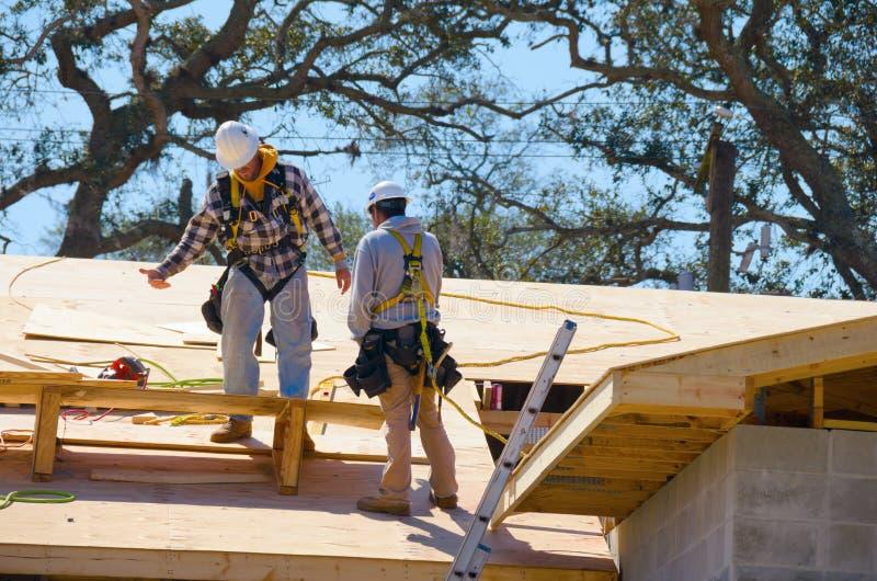 Εργάτες οικοδομών που φορούν τη σανίδα σωτηρίας λουριών ασφάλειας στοκ φωτογραφία με δικαίωμα ελεύθερης χρήσης