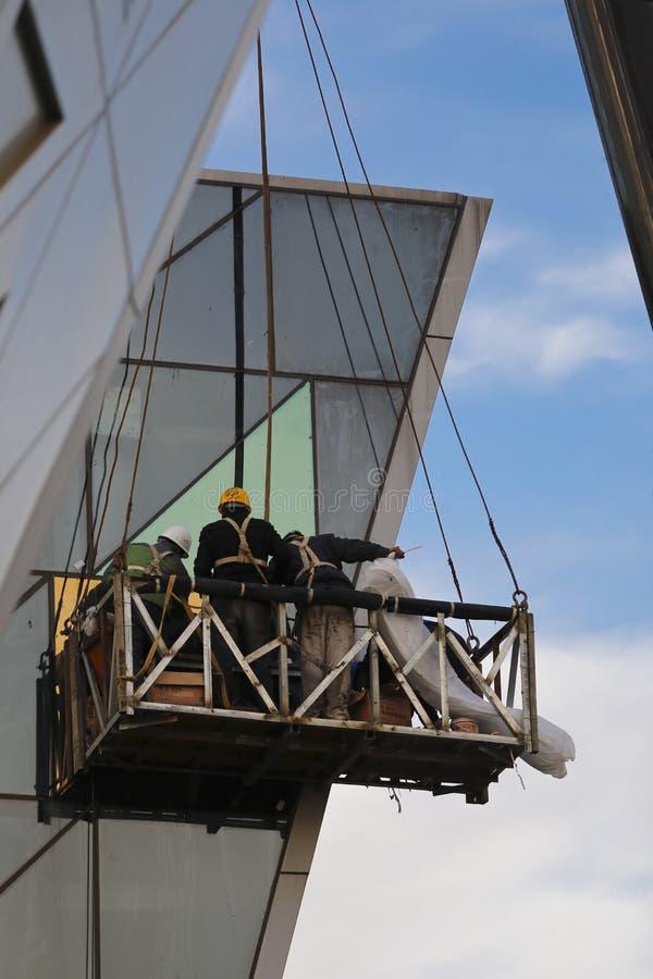 Εργάτες οικοδομών στο εξωτερικό γυαλί τοίχων ελέγχου στοκ φωτογραφία με δικαίωμα ελεύθερης χρήσης