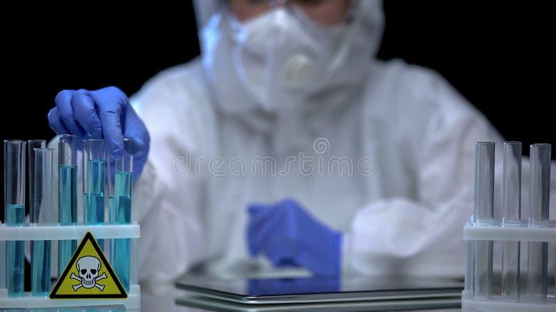 Εργάτης εργαστηρίου που επιθεωρεί δοκιμαστικούς σωλήνες με δηλητήριο για ιζήματα, διαδικασία διάλυσης στοκ εικόνα