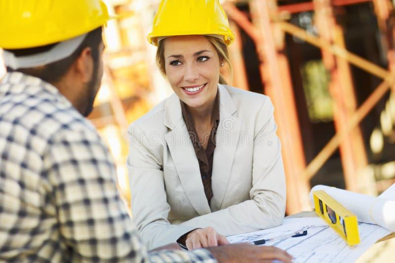 Εργάτης οικοδομών και θηλυκός αρχιτέκτονας στοκ φωτογραφία με δικαίωμα ελεύθερης χρήσης