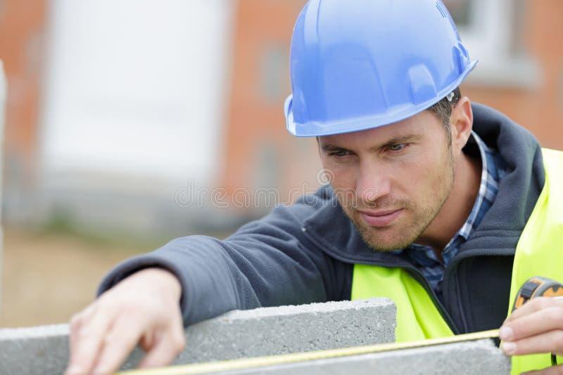 Εργάτης οικοδομών με το φραγμό τσιμέντου στοκ εικόνες