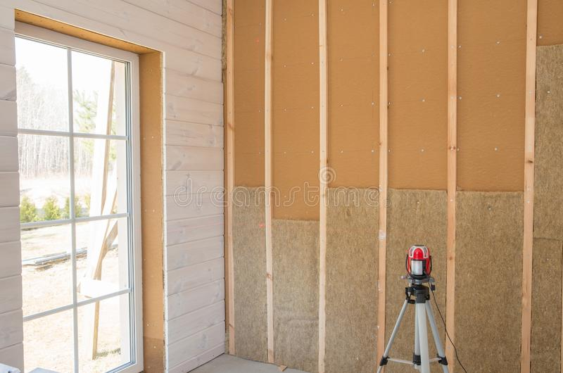 Εργάτης οικοδομών που μονώνει θερμικά το eco-ξύλινο σπίτι πλαισίων με τα ξύλινα πιάτα ινών και θερμότητα-που απομονώνει τη φυσική στοκ φωτογραφία
