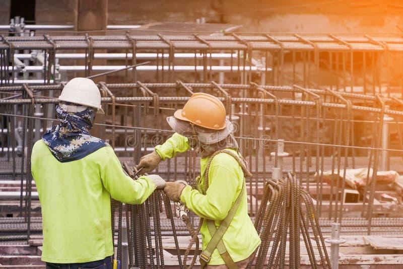 Εργάτης οικοδομών που φορά την πράσινη βοήθεια πουκάμισων ασφάλειας μεταξύ τους ήπιος χάλυβας χρήσης Δεσμεύστε τους μεγάλους φραγ στοκ εικόνες με δικαίωμα ελεύθερης χρήσης