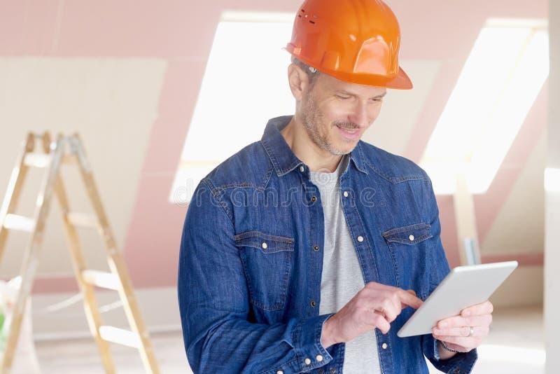 Εργάτης οικοδομών που χρησιμοποιεί την ψηφιακή ταμπλέτα εργαζόμενος στοκ εικόνες με δικαίωμα ελεύθερης χρήσης
