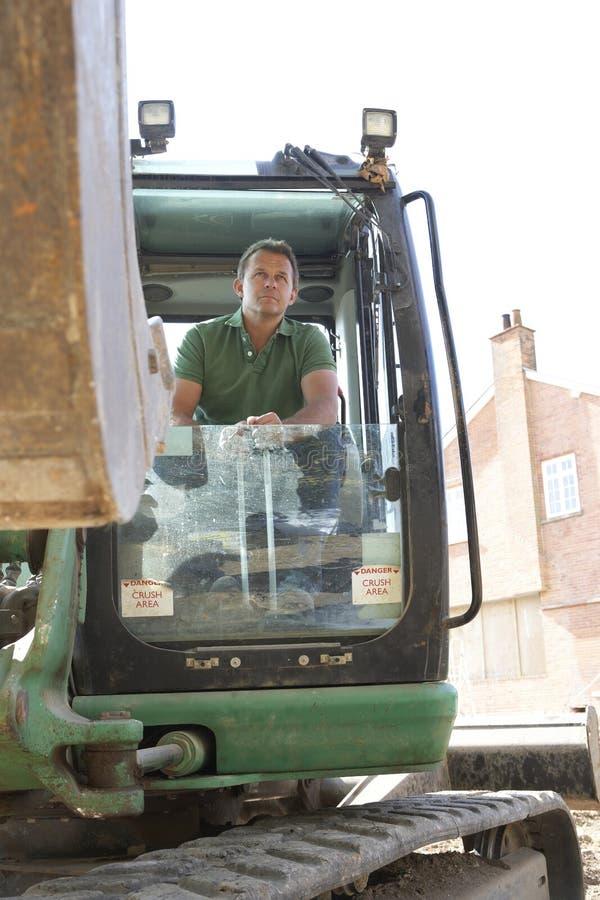 Εργάτης οικοδομών που χρησιμοποιεί Digger στοκ εικόνα