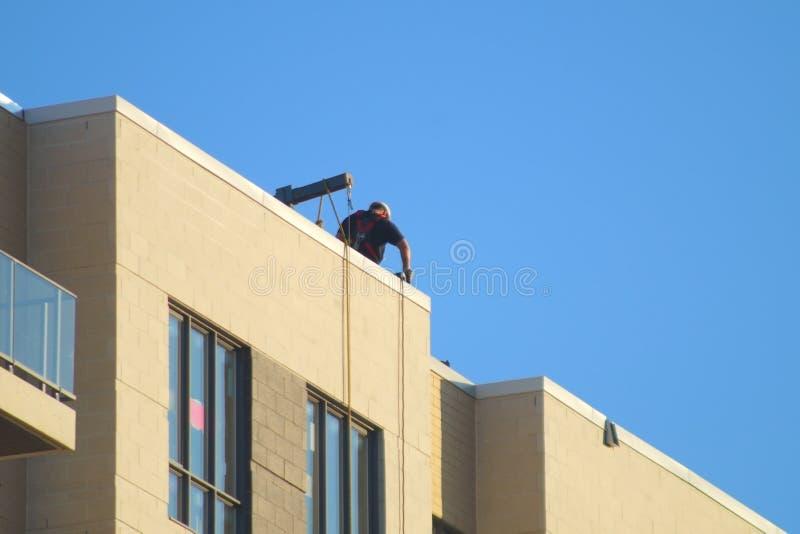 Εργάτης οικοδομών για το τοπ συγκεκριμένο κτήριο στεγών στοκ εικόνες