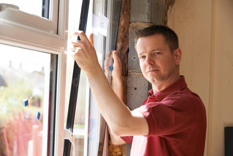 Εργάτης οικοδομών που εγκαθιστά τα νέα παράθυρα στο εσωτερικό στοκ φωτογραφία με δικαίωμα ελεύθερης χρήσης