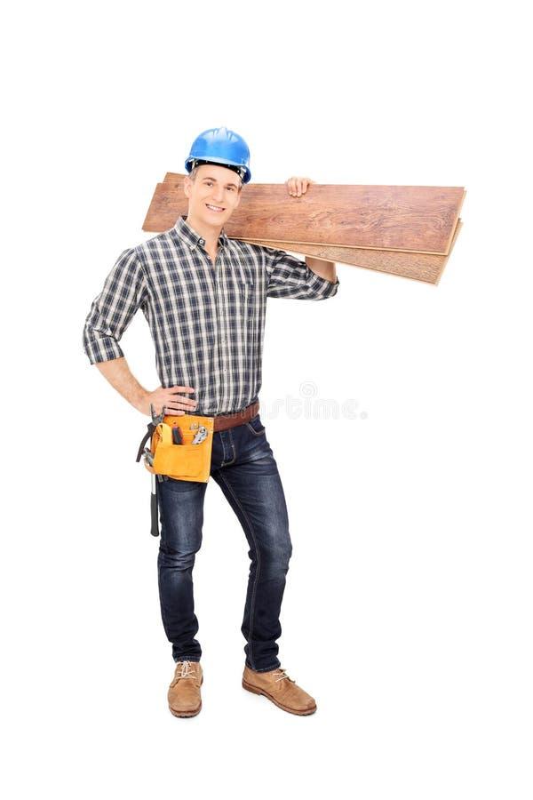 Εργάτης οικοδομών που κρατά μερικές σανίδες στοκ φωτογραφία
