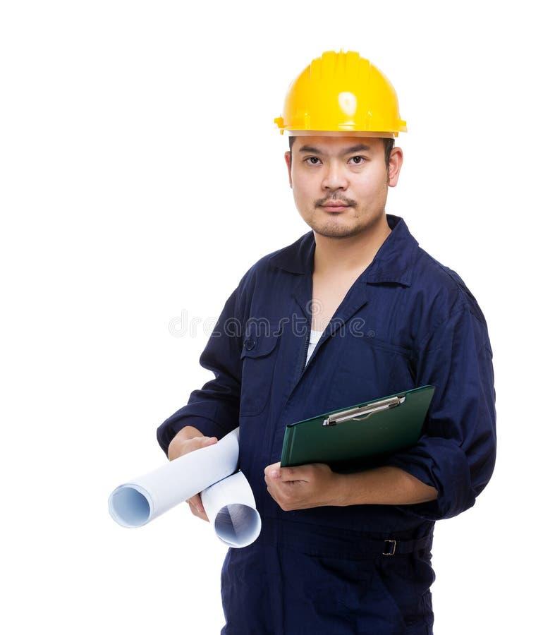 Εργάτης οικοδομών που κρατά το μαξιλάρι μπλε τυπωμένων υλών και αρχείων στοκ φωτογραφία με δικαίωμα ελεύθερης χρήσης