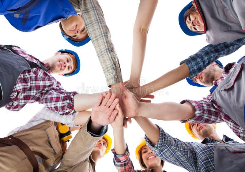 Εργάτης οικοδομών που συσσωρεύει τα χέρια στοκ εικόνες