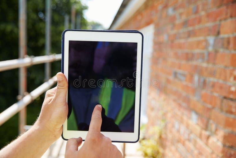 Εργάτης οικοδομών που χρησιμοποιεί την ψηφιακή ταμπλέτα στο εργοτάξιο στοκ εικόνα με δικαίωμα ελεύθερης χρήσης