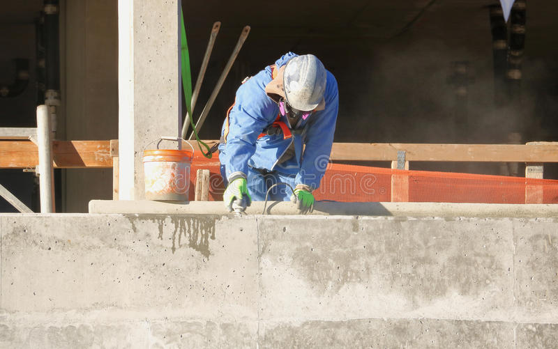 Εργάτης οικοδομών που χρησιμοποιεί Sander τσιμέντου στοκ φωτογραφία με δικαίωμα ελεύθερης χρήσης