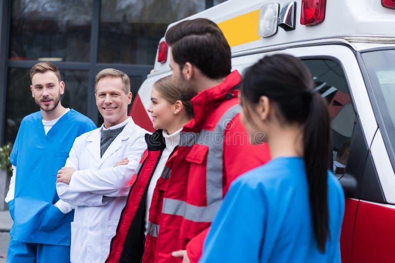 εργαζόμενη ομάδα paramedics που στέκεται μπροστά από το αυτοκίνητο και το κοίταγμα στοκ εικόνες