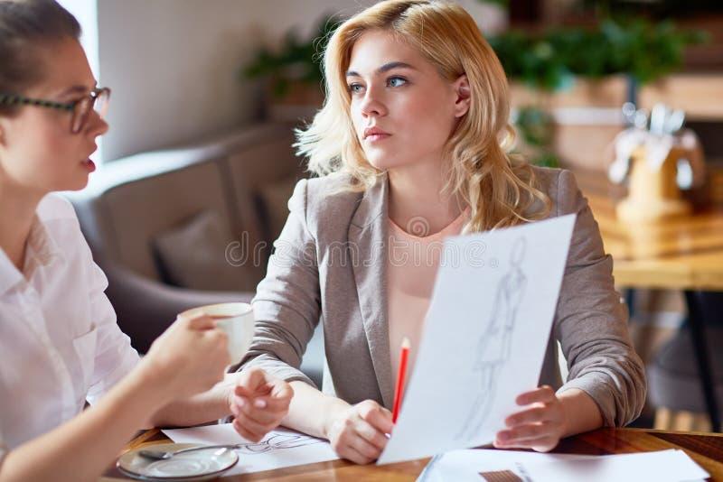 Εργαζόμενη συνεδρίαση στο άνετο καφέ στοκ εικόνα με δικαίωμα ελεύθερης χρήσης