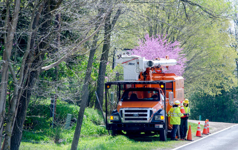 Εργαζόμενοι δέντρων στα φωτεινά σακάκια με το φορτηγό βραχιόνων στοκ φωτογραφία με δικαίωμα ελεύθερης χρήσης