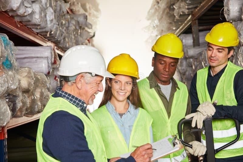 Εργαζόμενοι αποθηκών εμπορευμάτων ομάδας και συλλεκτικές μηχανές διαταγής στοκ εικόνα