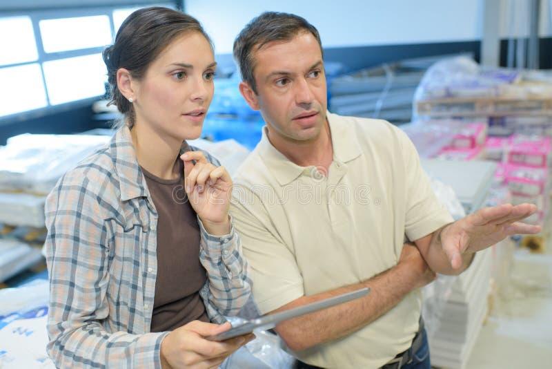 Εργαζόμενοι αποθηκών εμπορευμάτων που συζητούν με την περιοχή αποκομμάτων στην αποθήκη εμπορευμάτων στοκ φωτογραφία