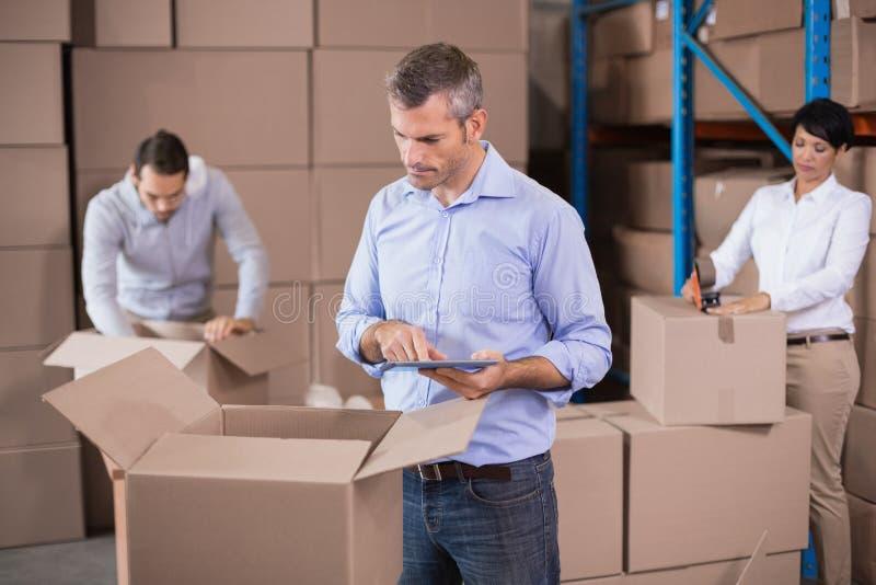 Εργαζόμενοι αποθηκών εμπορευμάτων που συσκευάζουν επάνω τα κιβώτια στοκ φωτογραφίες με δικαίωμα ελεύθερης χρήσης