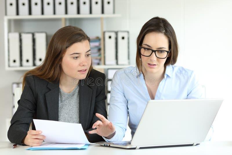 Εργαζόμενοι γραφείων που συγκρίνουν τα έγγραφα σε απευθείας σύνδεση στοκ εικόνες