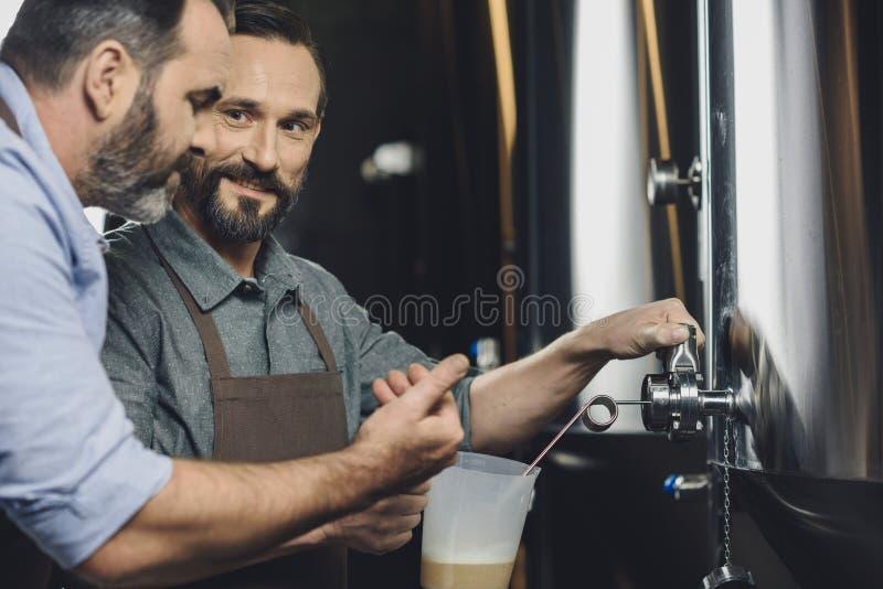 Εργαζόμενοι ζυθοποιείων που χύνουν την μπύρα στοκ φωτογραφίες με δικαίωμα ελεύθερης χρήσης
