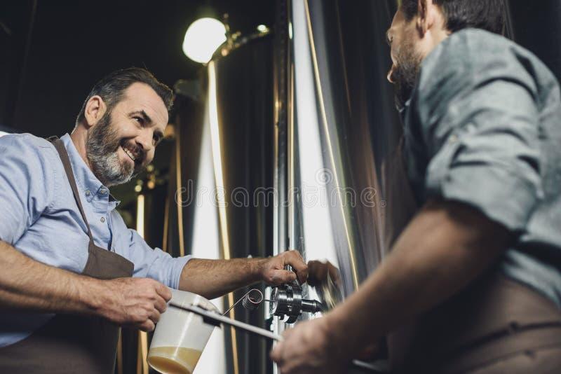 Εργαζόμενοι ζυθοποιείων που χύνουν την μπύρα στοκ φωτογραφία