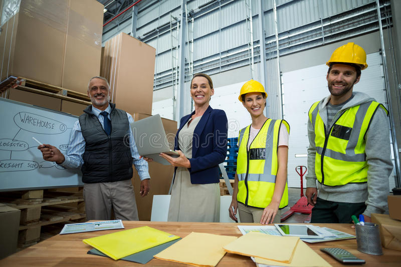 Εργαζόμενοι και διευθυντές αποθηκών εμπορευμάτων που στέκονται μαζί στην αποθήκη εμπορευμάτων στοκ φωτογραφία με δικαίωμα ελεύθερης χρήσης