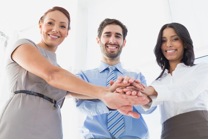 Εργαζόμενοι με το συσσωρευμένο χαμόγελο χεριών στοκ εικόνα