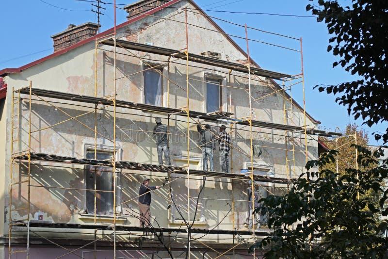 Εργαζόμενοι οικοδόμων που αναδημιουργούν την πρόσοψη να ενσωματώσει Lviv στοκ φωτογραφία
