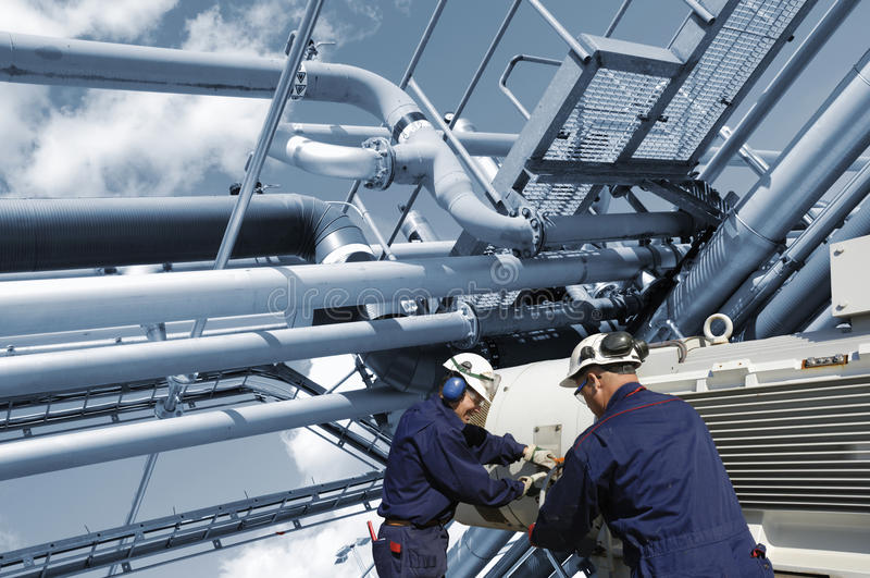 Εργαζόμενοι πετρελαίου και φυσικού αερίου με τις σωληνώσεις καυσίμων στοκ φωτογραφία