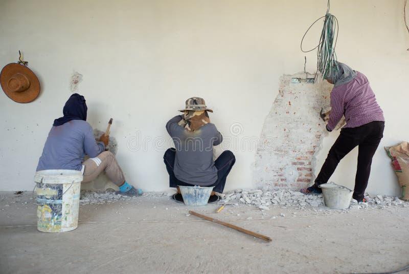 Εργαζόμενοι που αφαιρούν την επικονιασμένη επιφάνεια τσιμέντου στον πλινθοκτίστη στοκ φωτογραφία με δικαίωμα ελεύθερης χρήσης