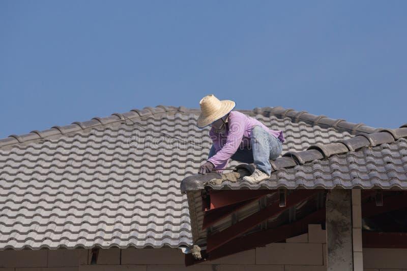 Εργαζόμενοι που εγκαθιστούν τα κεραμίδια στεγών για το εγχώριο κτήριο στοκ εικόνες