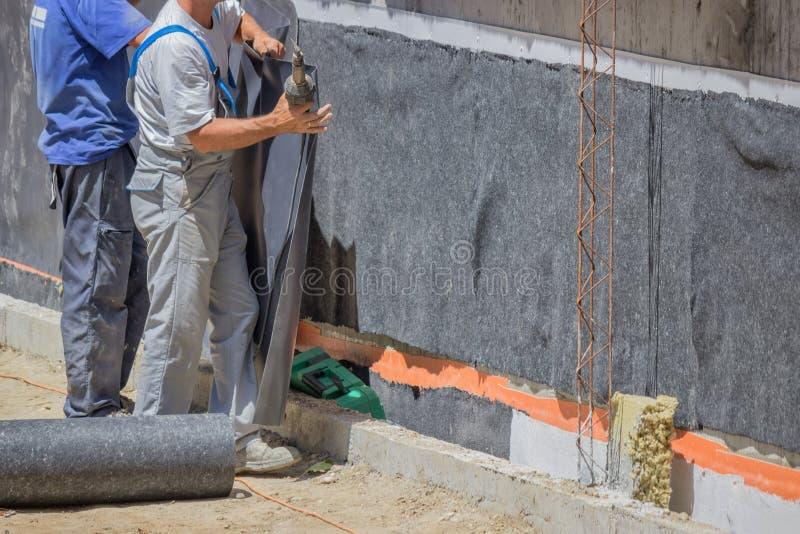 Εργαζόμενοι που εγκαθιστούν τη μόνωση τοίχων στοκ φωτογραφίες με δικαίωμα ελεύθερης χρήσης
