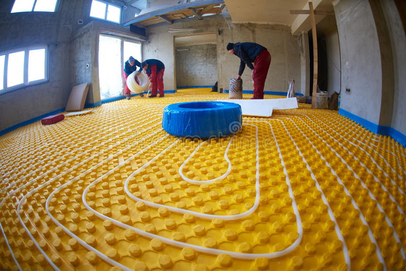 Εργαζόμενοι που εγκαθιστούν το σύστημα underfloor θέρμανσης στοκ εικόνα