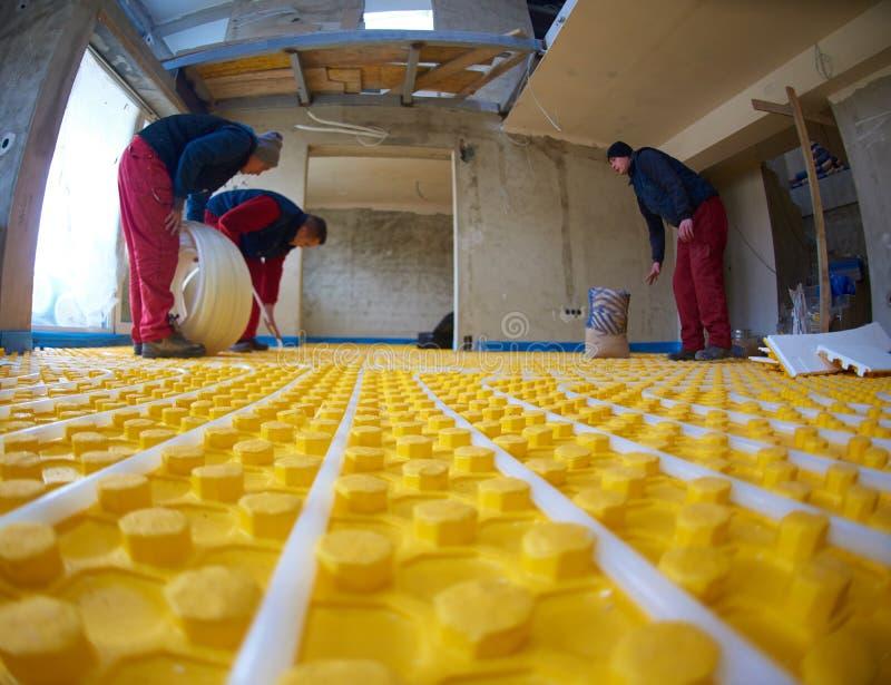Εργαζόμενοι που εγκαθιστούν το σύστημα underfloor θέρμανσης στοκ φωτογραφία