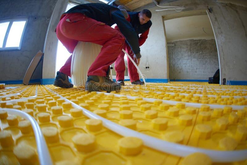 Εργαζόμενοι που εγκαθιστούν το σύστημα underfloor θέρμανσης στοκ εικόνες