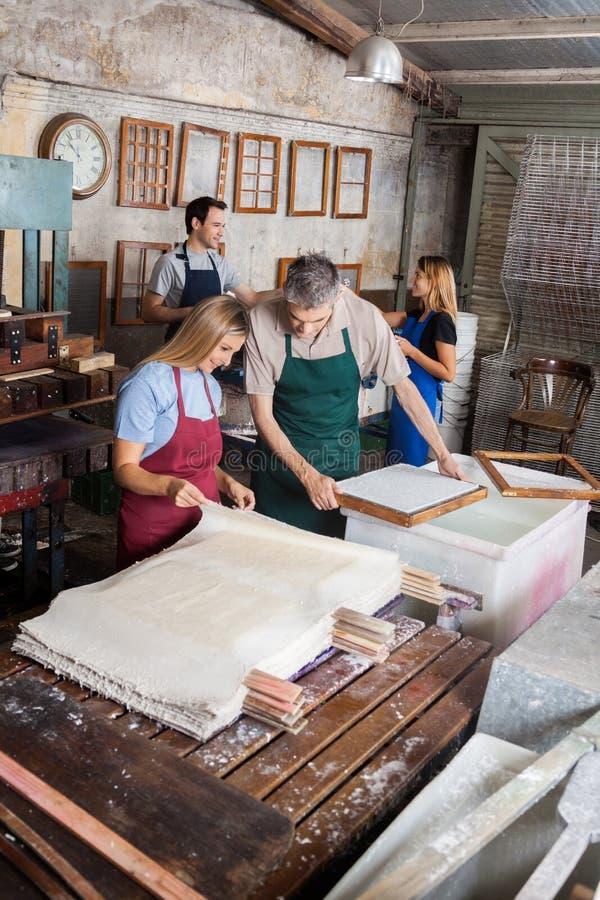Εργαζόμενοι που εξετάζουν την ξήρανση των εγγράφων στο εργοστάσιο στοκ φωτογραφίες