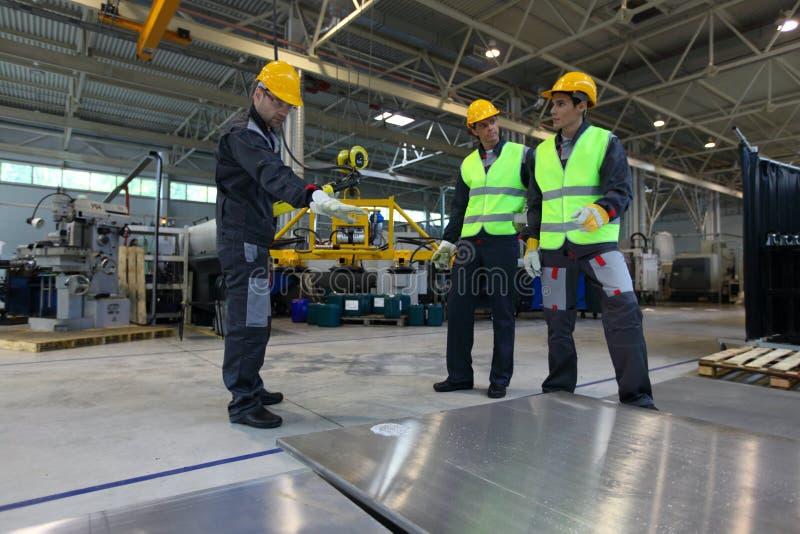 Εργαζόμενοι που εργάζονται με τα καταλύματα αλουμινίου στοκ εικόνα