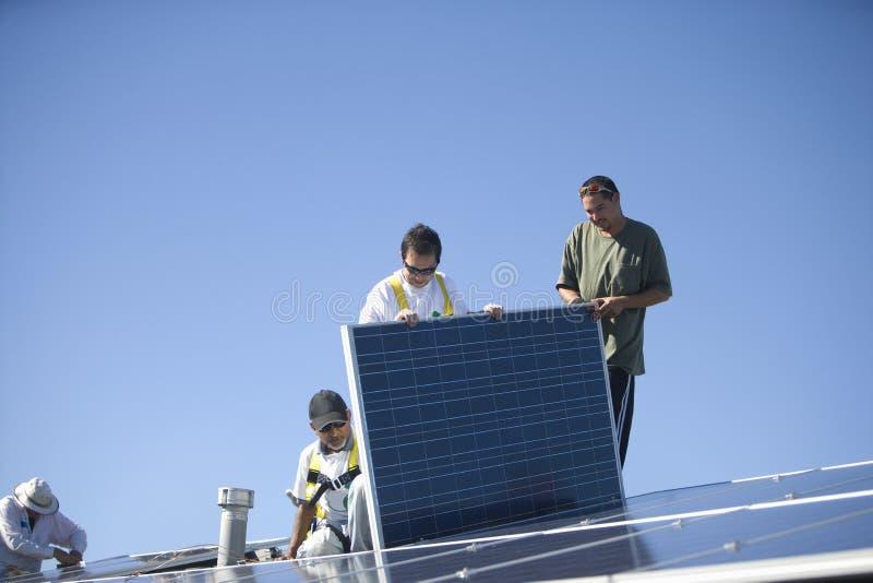 Εργαζόμενοι που εργάζονται στο ηλιακό πλαίσιο ενάντια στο μπλε ουρανό στοκ εικόνα με δικαίωμα ελεύθερης χρήσης