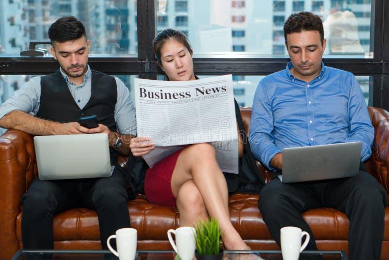 Εργαζόμενοι που χαλαρώνουν στον καναπέ με τη χρησιμοποίηση του φορητού προσωπικού υπολογιστή και την ανάγνωση της εφημερίδας στοκ φωτογραφίες