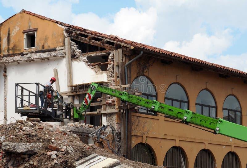 Εργαζόμενοι σε μια συλλεκτική μηχανή κερασιών στην εργασία κατά τη διάρκεια της ανακαίνισης ενός μερικώς κατεδαφισμένου κτηρίου στοκ φωτογραφίες με δικαίωμα ελεύθερης χρήσης