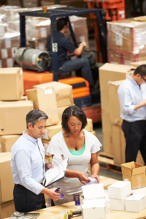 Εργαζόμενοι στην αποθήκη εμπορευμάτων που προετοιμάζουν τα αγαθά για την αποστολή στοκ εικόνα με δικαίωμα ελεύθερης χρήσης