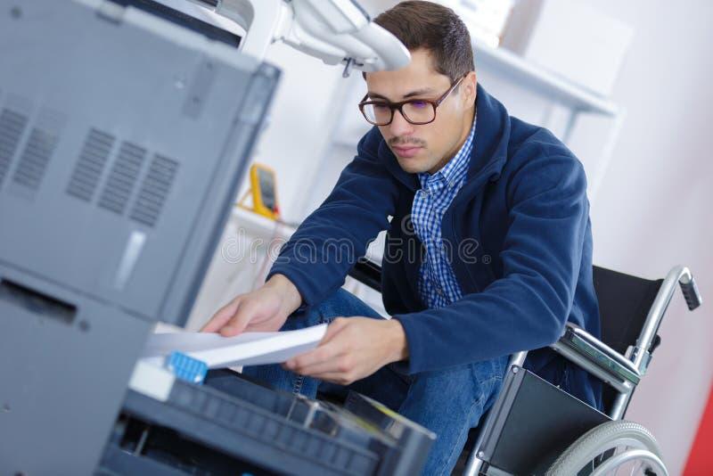 Εργαζόμενος αναπηρικών καρεκλών που βάζει το έγγραφο σωρών στον εκτυπωτή στοκ φωτογραφίες