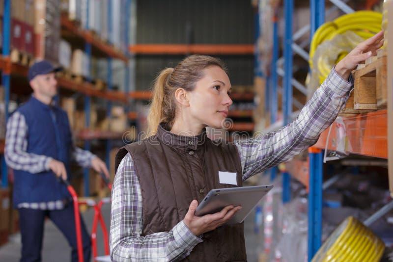 Εργαζόμενος αποθηκών εμπορευμάτων θηλυκών που ελέγχει τα καλώδια αποθεμάτων στοκ φωτογραφία