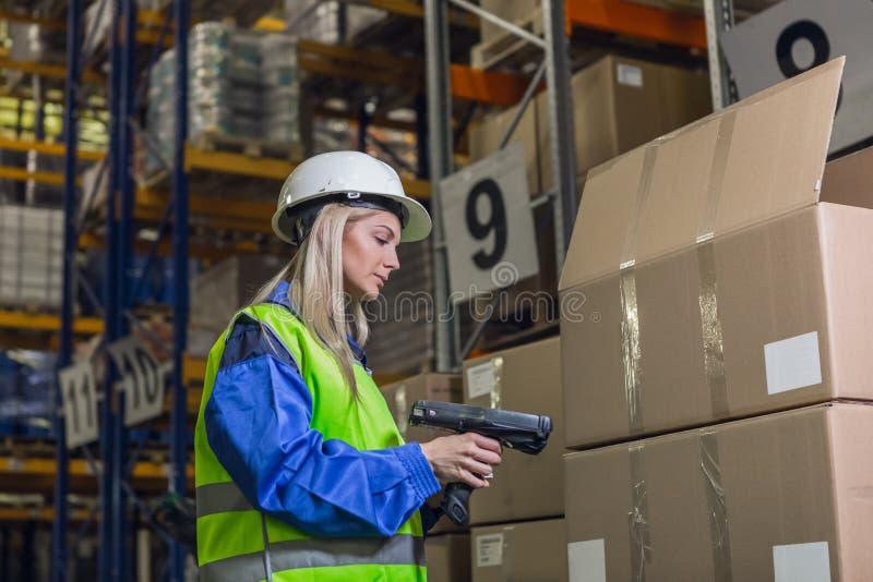 Εργαζόμενος αποθηκών εμπορευμάτων θηλυκών που χρησιμοποιεί τον ανιχνευτή στοκ εικόνα