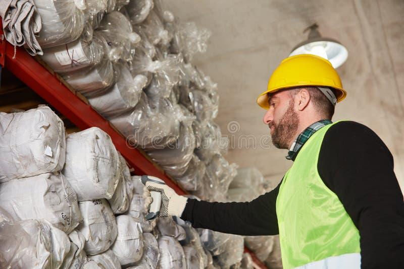 Εργαζόμενος αποθηκών εμπορευμάτων με έναν ανιχνευτή στην αποθήκη εμπορευμάτων ταπήτων στοκ εικόνα