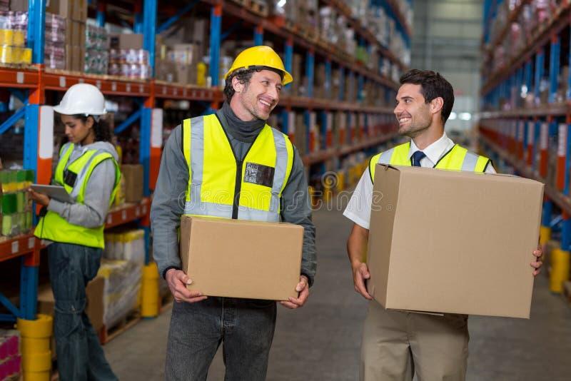 Εργαζόμενος αποθηκών εμπορευμάτων που αλληλεπιδρά ο ένας με τον άλλον στοκ εικόνα
