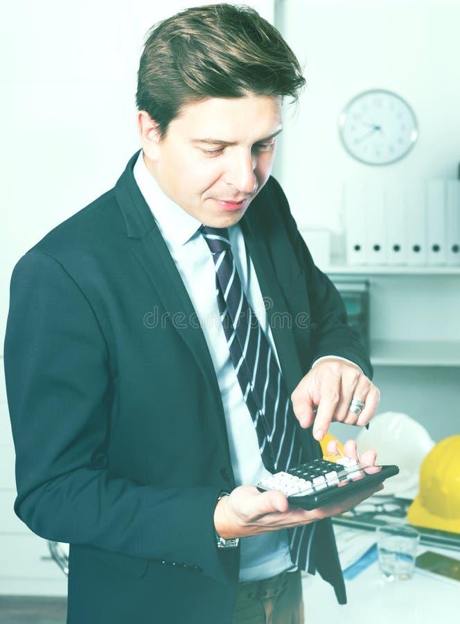 Εργαζόμενος ατόμων που υπολογίζει στο γραφείο στοκ φωτογραφία