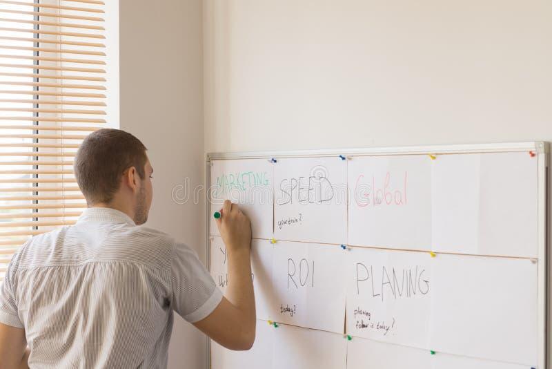 Εργαζόμενος γραφείων αρσενικών που γράφει στο χρονοπρογραμματιστή Whiteboard στοκ εικόνες