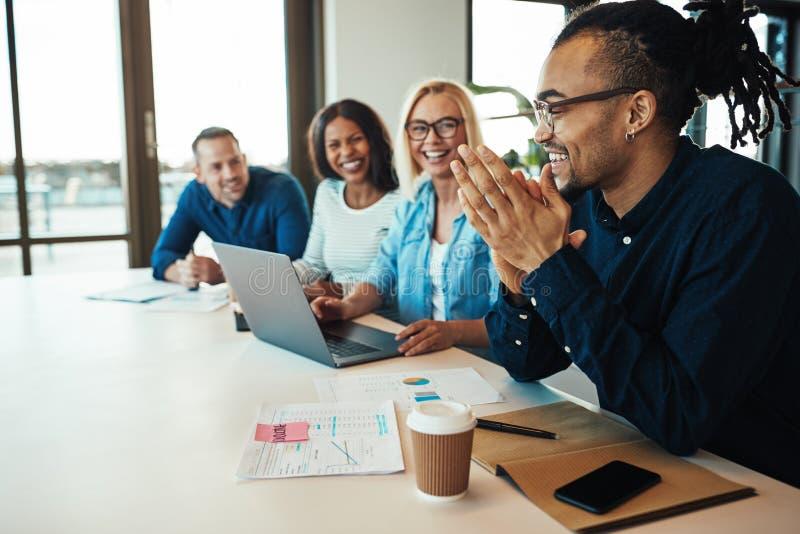 Εργαζόμενος γραφείων αφροαμερικάνων που γελά με τους συναδέλφους σε ένα mee στοκ εικόνα